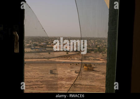 A view of the skyline of Ouagadougou, the capital of Burkina Faso, through a broken window in the Monument of National Heroes - Stock Image