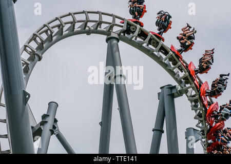 roller coaster ride inside amusement park on an overcast day - Stock Image