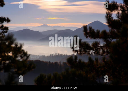 Scenic view of mountains in foggy weather during sunset - Stock Image