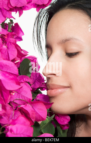 Close-up of a woman smelling flowers - Stock Image