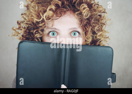 Close-up portrait of a beautiful and young funny woman with blue eyes and curly blonde hair, she is behind of a agenda or ebook and she is surprised - Stock Image