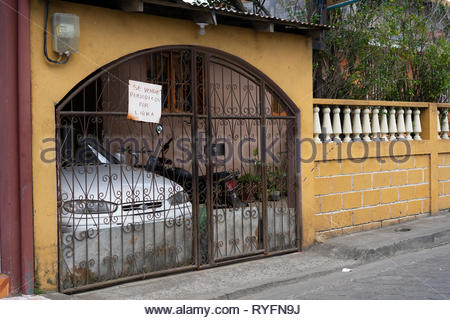 Magazines offered for sale by the pound at a house with a fenced in car port. - Stock Image