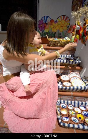 Mother and toddler shopping for ceramics, Mijas Pueblo, Costa del Sol, Andalucia, Spain - Stock Image