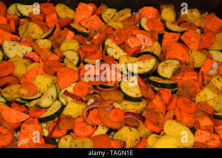 healthy oven vegetables before baking, raw organic cutting oven vegetables flavored with various herbs and oil before baking - Stock Image