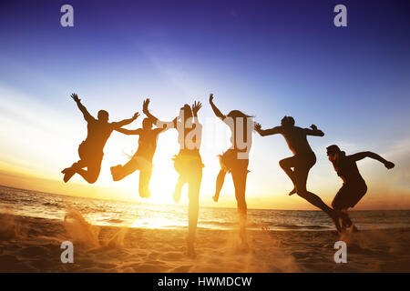Happy friends jumps beach sunset. Friendship or team concept - Stock Image