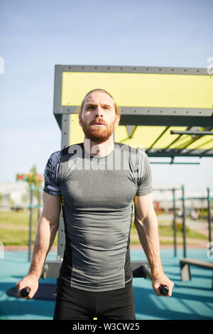 Concentrated tenacious man in sportswear exhaling while doing pull-ups on bars outdoors - Stock Image