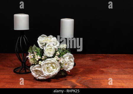 Beautiful bouquet of arranged flowers white candles on a holder on a wooden table. mothers day, Easter, valentines, birthday, Christmas, - Stock Image