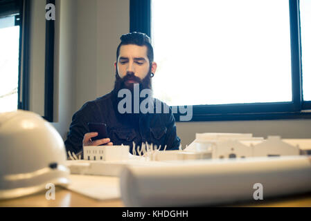 Architect looking at smartphone in office - Stock Image