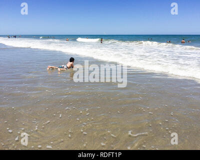 Boy playing on beach, alone (child lying in water, alone) - Cocoa Beach, Florida USA - Stock Image