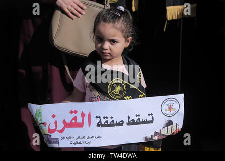 A Palestinian girl holds a banner reading 'Down at the Bahrain Conference' during a protest at the Bahrain Peace Plan workshop in southern Gaza Strip. - Stock Image