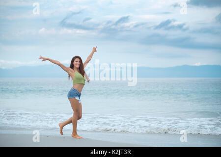 Happy hispanic woman enjoying beach walk - Stock Image