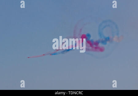 Red Arrows  with curling colour trail - Stock Image