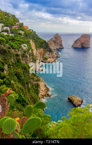 Sea view by Capri island, Italy. The rocks are famous as Faraglioni rock. Locals say that they have seen sirens on this rock and often hear their whis - Stock Image