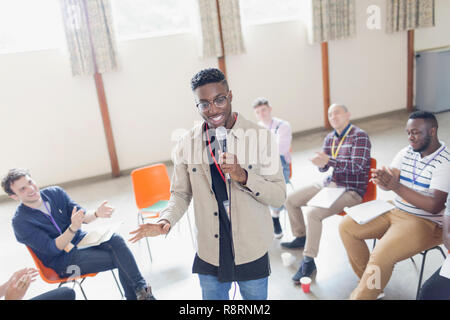 Man with microphone leading group therapy - Stock Image