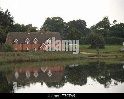 Country cottage reflected in Beaulieu River at Beaulieu, New Forest, Hampshire, England, UK - Stock Image
