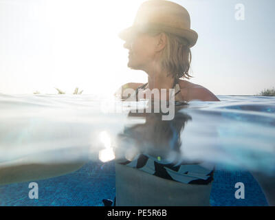 A woman enjoys a swim in an infinity pool on holiday, wearing a straw hat - Stock Image
