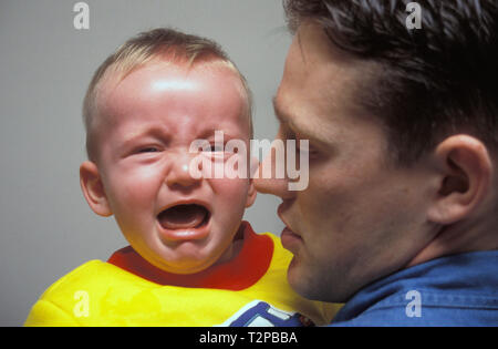 father holding screaming baby boy - Stock Image