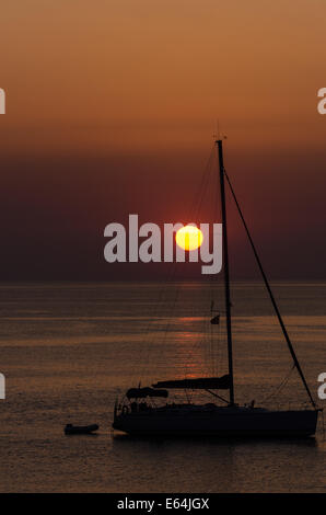 Silhouette of a yacht at anchor and rising sun in calm bay - Stock Image