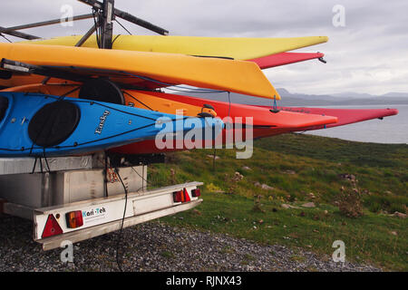 Colourful kayaks loaded onto a large trailer on a track in wild open countryside waiting to be used on the open sea - Stock Image