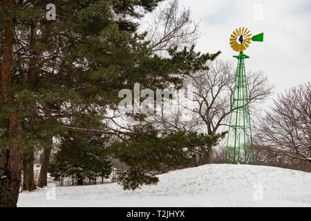 A yellow and green windmill in Sedgwick county park after a late winter snow. Wichita, Kansas, USA - Stock Image