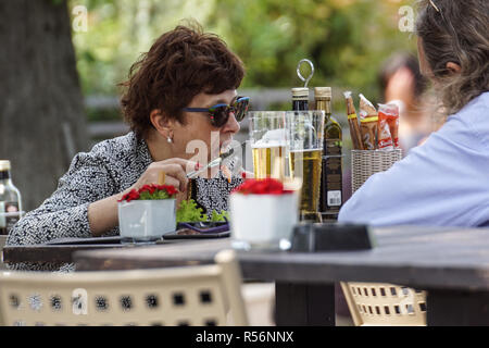 MILAN , ITALY 18 JUNE 2018 : A woman eats a food during a day at the restaurant . - Stock Image