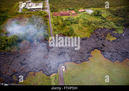An aerial view looking at a pahoehoe lobe of molten lava in the Puu Oo vent flow field covers Cemetery Road at the - Stock Image