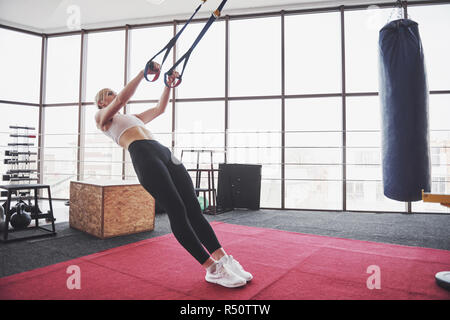 Women doing push ups training arms with trx fitness straps in the gym Concept workout healthy lifestyle sport - Stock Image