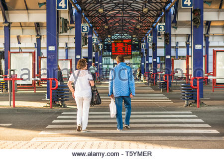 Poznan, Poland - April 18, 2019: Man and woman with bags walking on a zebra crossing on the Rataje public transport bus station. - Stock Image