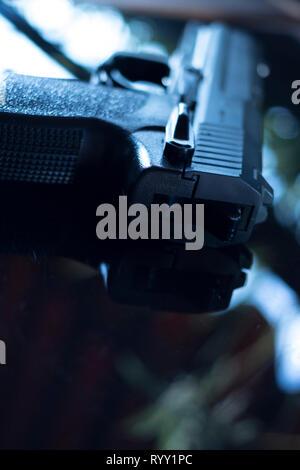 Automatic pistol handgun in artistic light effect moody atmospheric photo creative artistic closeup - Stock Image