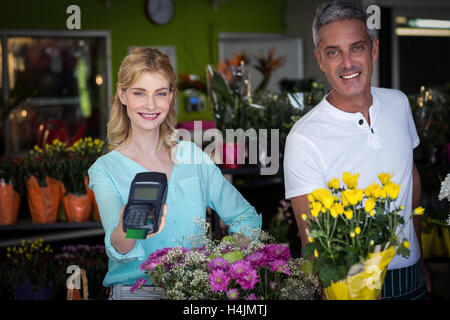 Smiling florist showing credit card terminal in flower shop - Stock Image