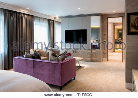Purple sofa by flat panel television in bedroom - Stock Image