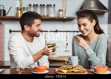 Image of a happy young loving couple at the kitchen have a breakfast. - Stock Image