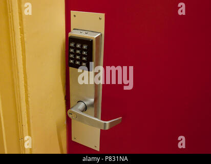 A keypad on a door is batter operated, punch in a code and it will open - Stock Image