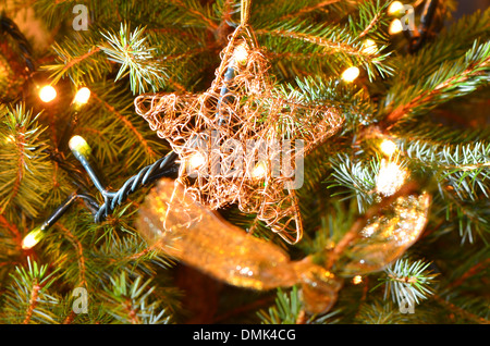 Christmas decoration, golden star and white lights in tree - Stock Image