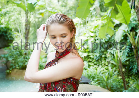 Young woman with wet hair by tropical trees - Stock Image