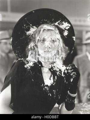 Woman with cream pie thrown in her face - Stock Image