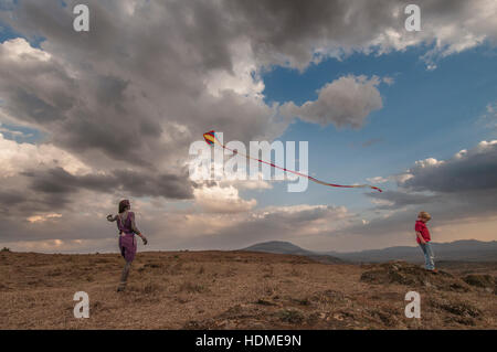 Maasai warrior flying a kite with a child. Kenya, Africa. - Stock Image