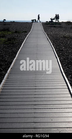 Three silhouetted unrecognisable people and a baby in a pram walking across the end of a long straight wooden pathway with a pebble beach on both side - Stock Image