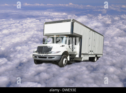 delivery truck flying above clouds - Stock Image
