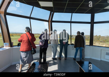 Visitors looking out from the Control Tower at Greenham Common, formally an American airbase with nuclear weapons, near Newbury, Berkshire, UK - Stock Image