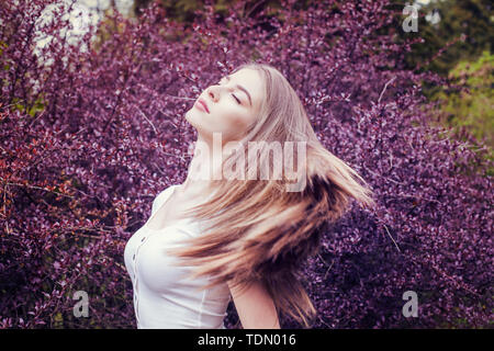 Pretty young woman with long straight hair portrait against purple flowers background - Stock Image