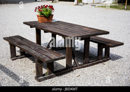 Brown bench with red flowers decorating it - Stock Image