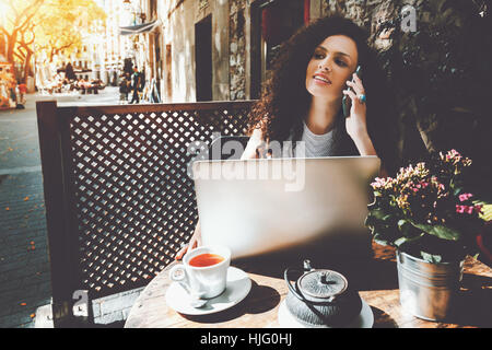 Young beautiful curly brunette calling mobile phone while sitting with portable laptop in street cafe, charming - Stock Image