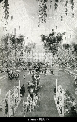 Coaches drawn by four horses at the annual International Horse Show, in the glass-roofed building at Olympia, West London, with spectators seated in the background. - Stock Image