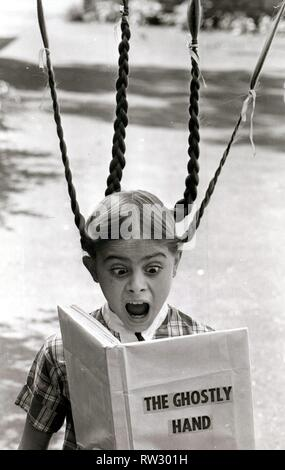 A girl's pigtails stand on end in terror as she reads a scary ghost story August 1978 - Stock Image