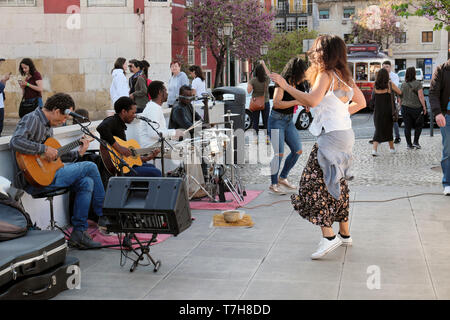 Tourists watch woman dancing in the street to the music of a group of musicians playing guitars drums Alfama district of Lisbon Portugal  KATHY DEWITT - Stock Image