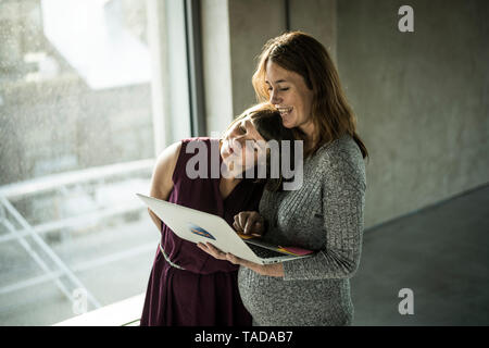 Friends working toghether in office, discussing work, using laptop - Stock Image