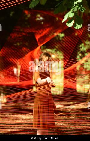 Llanrwst, Wales, UK. 27th June, 2019.  MIST, an outdoors art installation by Sébastien Preschoux at Ffin y Parc gallery on the outskirts of Llanrwst in north wales.   Woven  from 14km of orange thread suspended in the trees, the work is the UK public premiere for this French artist and bursts into life in the morning sun. The project was curated by Migrations, an organization dedicated to bringing ground breaking  art to Wales   Photo credit Keith Morris / Alamy Live News - Stock Image