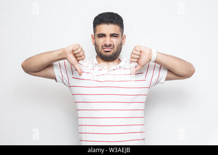 I don't like this. Portrait of displeased bearded young man in striped t-shirt standing with thumbs down dislike sign gesture and looking at camera. i - Stock Image