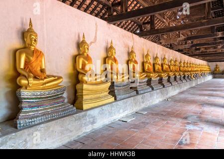 Row of golden buddha statue sitting at Wat Phutthaisawan temple in Ayutthaya Historical Park, Phra Nakhon Si Ayutthaya - Stock Image